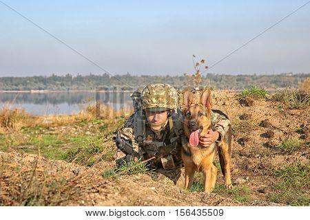 Soldier with german shepherd dog at military firing range