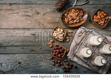 Vegan milk from nuts in glass bottles with various nuts on old wooden background, top view with copy space