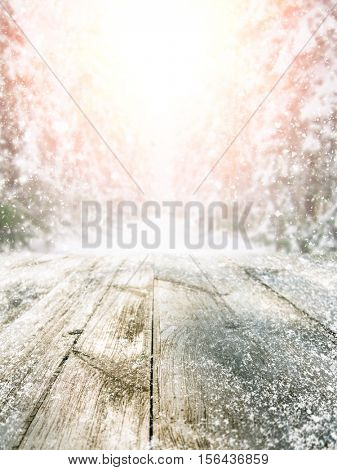 Empty wooden table at snowy winter forest during sunset