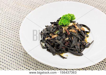 Fresh black aglio olio pasta with garlic and chilli