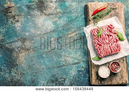Raw minced meat with olive oil and seasoning on paper over blue stone background. top view with copy space.
