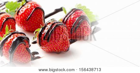 Fresh Strawberries  In Chocolate Sauce On A White Plate.