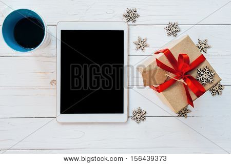 Top View Tablet, Cup Coffee, And Gift Box With Snowflakes On White Wood Background For Christmas And