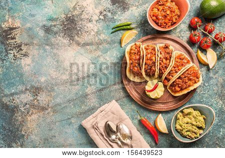 Mexican tacos with ground beef, beans and salsa on cutting board over blue stone background. Top view
