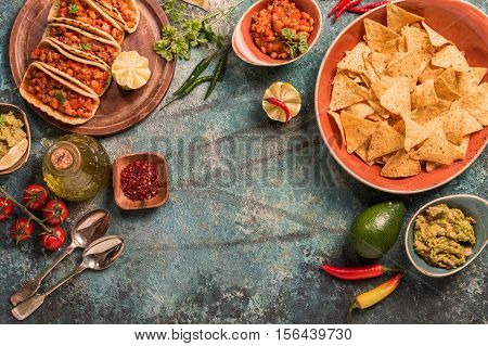 traditional mexican food - tacos with meat, beans and salsa and nachos with sauce. Top view