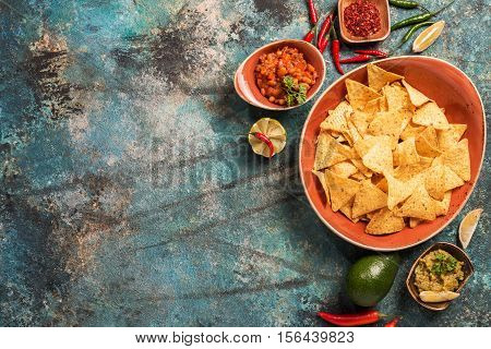 Nachos in plate with guacamole, ground beef and other sauces on blue stone background, top view
