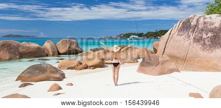 Woman arms rised, wearing black bikini and beach hat, enjoying amazing view on Anse Lazio beach on Praslin Island, Seychelles. Summer vacations on picture perfect tropical beach concept.