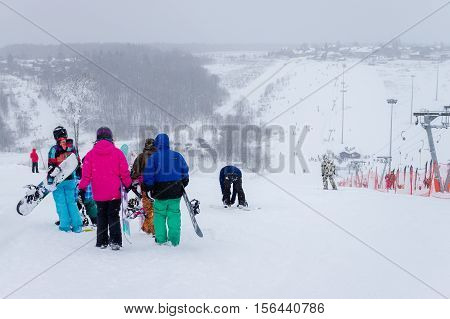 MOSCOW RUSSIA - JANUARY 25 2015: Ski club Leonid Tyagachev-oldest ski resort in Moscow region and training base for Russian national teams.People with snowboards on ski slope.Blurred in perspective