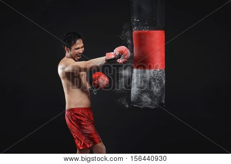 Serious Asian Male Boxer Training With Punching The Punching Bag