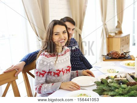 Couple of young handsome caucasian man and woman sitting on a table having christmas meal. Christmas food celebration concept