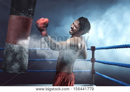 Asian Man Boxer Practicing With Punching Bag