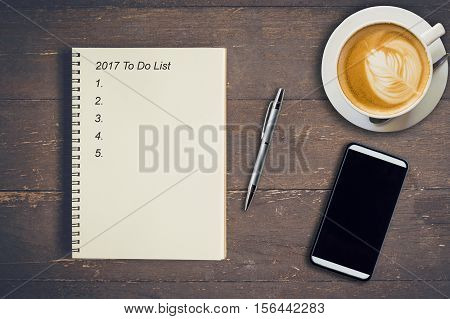 Business Concept - Top View Notebook Writing 2017 To Do List, Pen, Coffee Cup, And Phone On Wood Tab