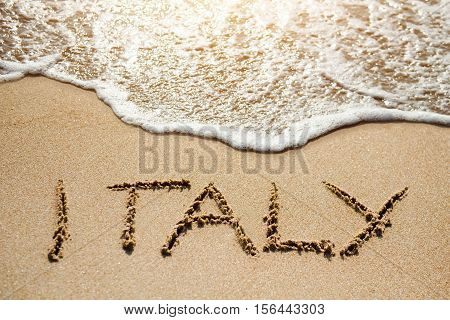 Italy written on the sand beach near sea - travel holiday concept