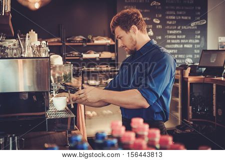 Handsome barista preparing cup of coffee for customer in coffee shop