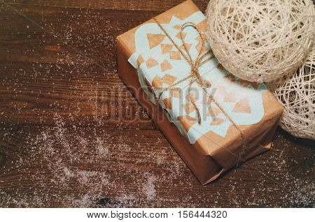 Christmas gift lies on a wooden table packed in kraft paper with a blue snowflake