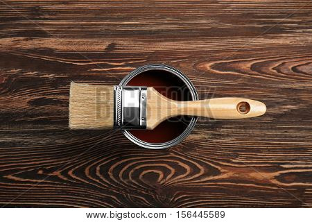 Paint and brush on wooden background, top view