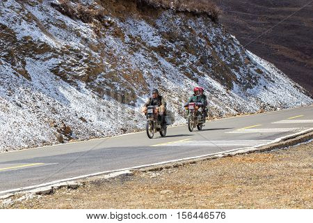 SICHUAN CHINA - MAY 02 2016 : Biker motorcycle on the road beautiful winter in Tibet under snow mountain Sichuan China