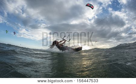 A kite surfer rides the waves in sunset