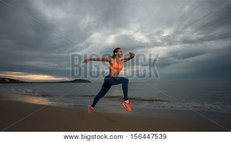 Sport woman runig on the beach and reflected in the water