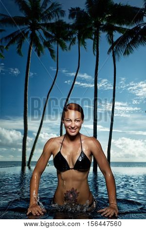 Woman swimming in the pool beautiful against coast tropical palm trees