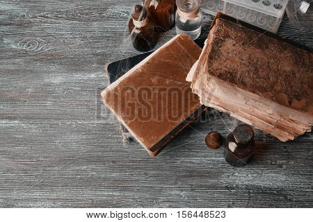 Old books with vintage bottles on wooden background, closeup