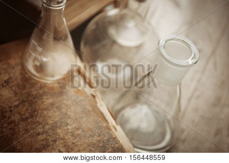 Glass flasks and old book on wooden background, closeup