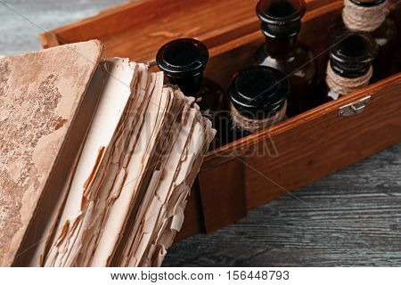 Vintage glass bottles in wooden box with old book, closeup
