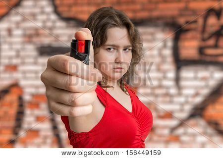 Young Woman Is Defending With Pepper Spray. Self Defense Concept