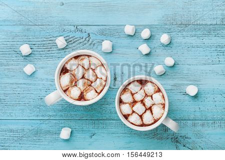 Two cups of hot chocolate on blue rustic table from above. Delicious winter drink. Flat lay.