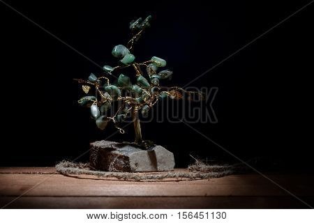 souvenir of a tree and colored green leaves of malachite stones isolated on darkbackground
