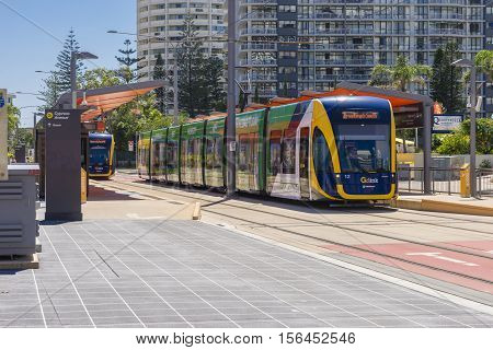 Gold Coast, Australia - September 23, 2016: View of trams stopped at one of the light rail stations with skyscrapers behind in Gold Coast during daytime.