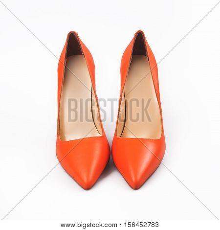 Orange high heels pump shoes over white