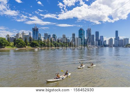 Brisbane, Australia - September 25, 2016: View of tourists on kayak tour along the Brisbane River with skyline in the background during daytime. Kayaking is a fun way to see Brisbane.