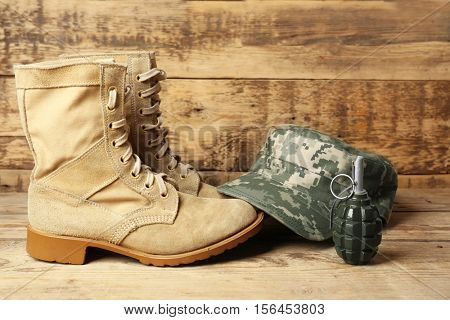 Pair of combat boots, military cap and grenade on wooden background, close up