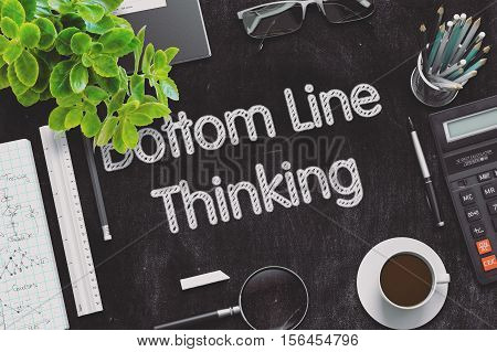 Bottom Line Thinking. Business Concept Handwritten on Black Chalkboard. Top View Composition with Chalkboard and Office Supplies. 3d Rendering. Toned Illustration.