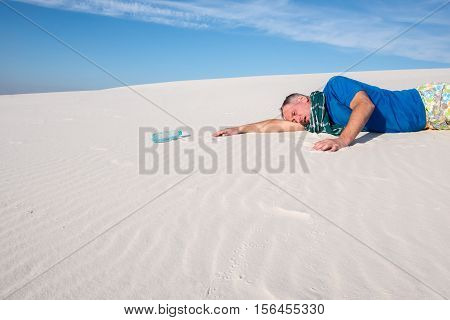 Man lost in the desert suffering from thirst crawls to the bottle with water.