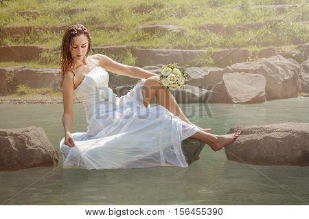 Romantic young bride on the day of their wedding on the lake - landscape