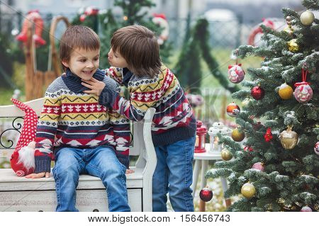 Two Adorable Children, Boy Brothers, Having Fun Outdoors In The Garden On Christmas