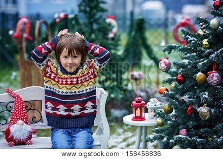 Cute Adorable Child, Boy, Having Fun Outdoors In The Garden On Christmas