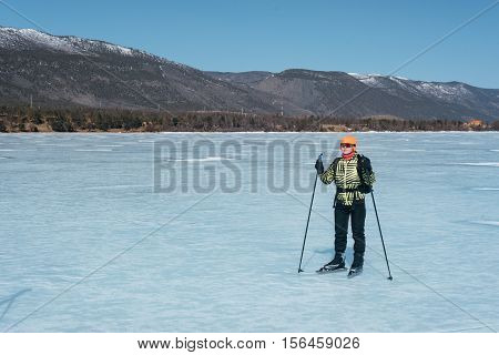 Tourists travel to Norway hiking ice skating on the frozen lake. Special long skate for long distances. Mounting under the ski boots. Location of Lake Baikal action. The Russian called Bayes or Loft .