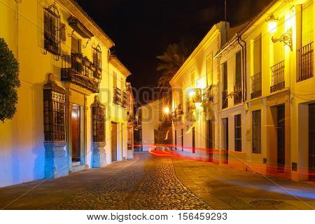 Narrow dark alley in the old town at night illuminated in Ronda, Andalusia, Spain