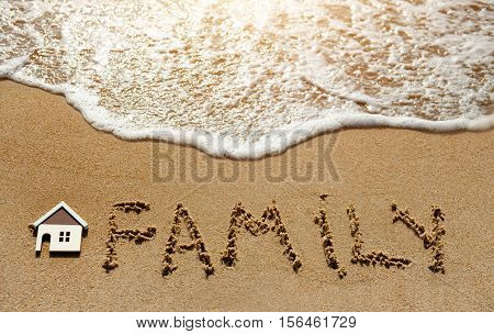 House and family on the sand beach near sea - property investment concept