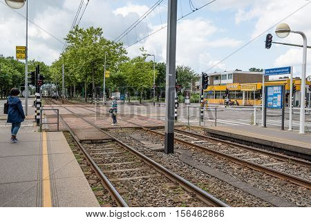 Amsterdam Netherlands - August 1 2016: People crossing the tracks of the Tram. The Amsterdam Tram is one the largest tram network in Europe.