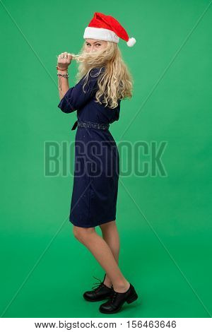 Young blonde woman in a christmas cap looking coquettishly and making a beard of the hair chroma key green screen