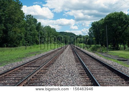 Two railroad tracks running off into the distance. Riverbank of Mississippi, Illinois, USA