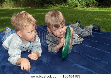 Two little boys are lying on an air mattress and considering playing frisbee for the first time