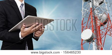 Businessman working on digital tablet, with satellite dish telecom network on telecommunication tower on blue sky with sunshine, telecommunication in business and development