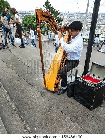 PARIS, FRANCE-JULY 28, 2016:  Harp player on steps in front of Sacre Coeur in Paris, France
