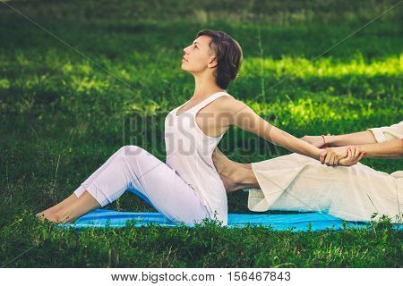 Young man and woman dressed in a white robe doing thai massage with yoga exercises sitting on the mat. Sunny summer park with green lawn in the background
