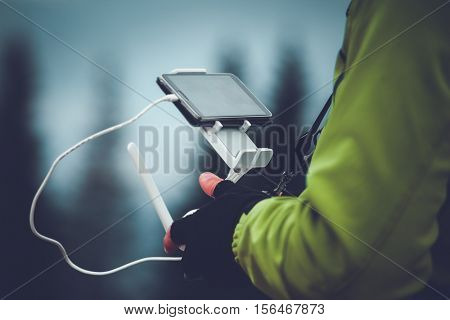 Man in green jacket operating a drone using a remote controller. Winter holidays in mountains. Close up picture. Bukovel, Carpathians, Ukraine, Europe. Exploring beauty world